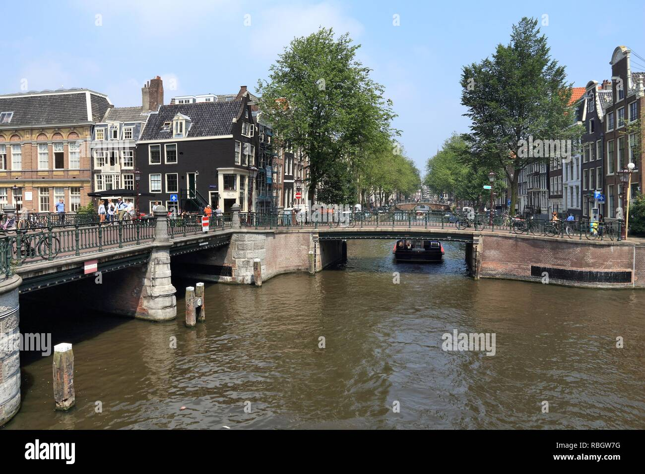 AMSTERDAM, NETHERLANDS - JULY 7, 2017: People visit Leidsegracht and Prinsengracht canal crossing in Amsterdam, Netherlands. Amsterdam is the capital  - Stock Image
