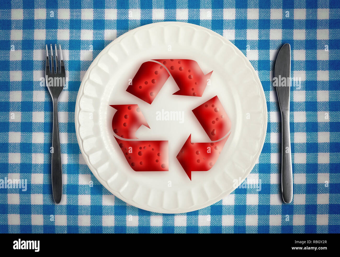 Autophagy during fasting concept with cells in red renewal symbol on white plate on blue checkered table cloth with knife and fork, top view - Stock Image