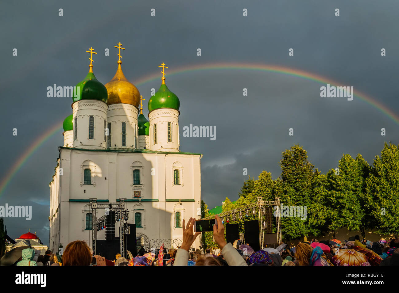 Rainbow over the snow-white temple in the dramatic sky. Cathedral Square of the city of Kolomna of the Moscow region. People take pictures of a rainbo Stock Photo