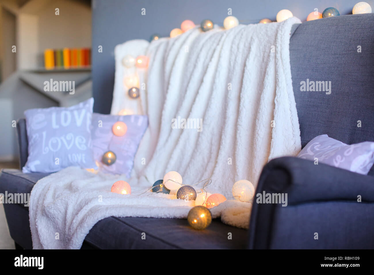 Yellow garlands on sofa and white plaid. - Stock Image