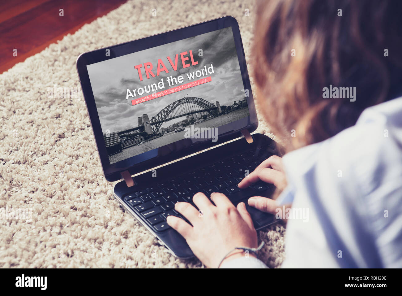 Travel agency website in a laptop screen while woman uses it to book a travel at home. - Stock Image