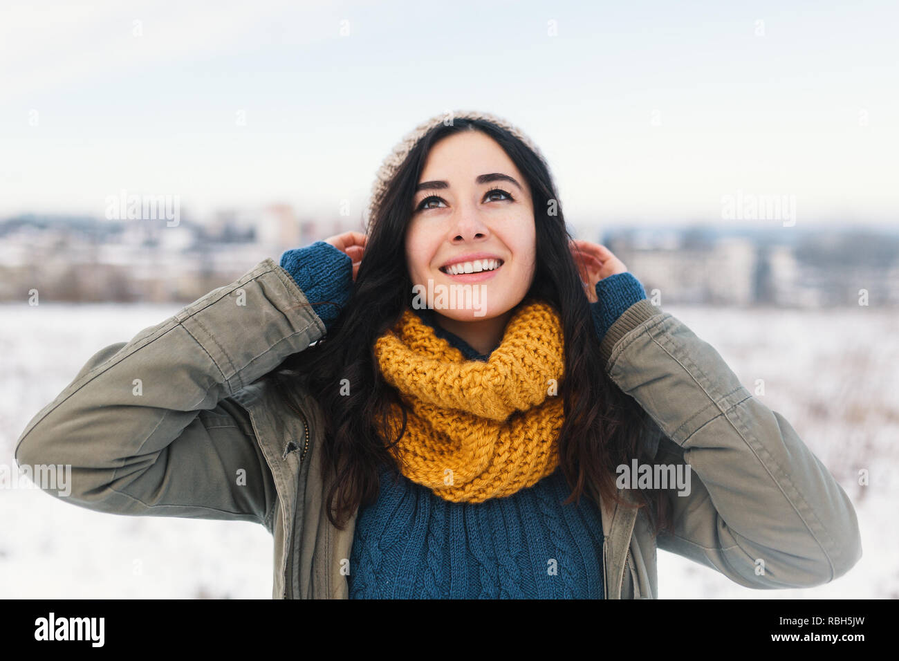 Heart melting winter portrait of pretty young woman enjoying winter, vacation, snow, holiday and her comfy, beautiful clothes and a warm woollen sweat - Stock Image