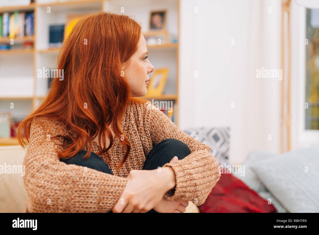 Young redhead woman looking away to stare out of a window as she clasps her knees while sitting on a comfy sofa at home - Stock Image