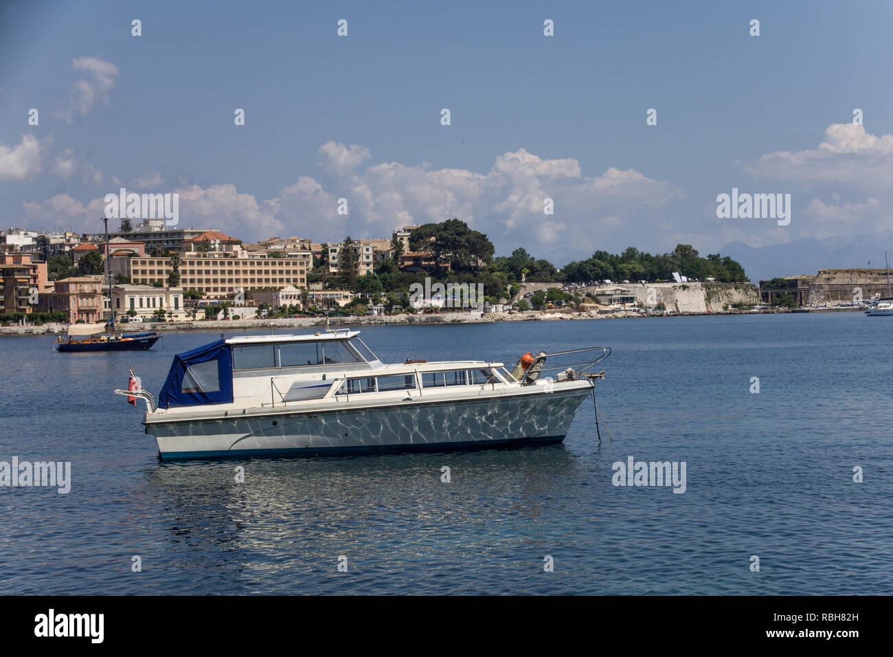 SideView Shot of Unmanned Double Deck Boat on Water under Cloudy Blue Sky. Establishments, Structures and Trees as Background. Vacation Destination Id - Stock Image