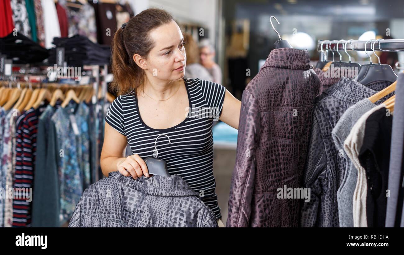 Cheerful attractive woman choosing new coat in showroom - Stock Image