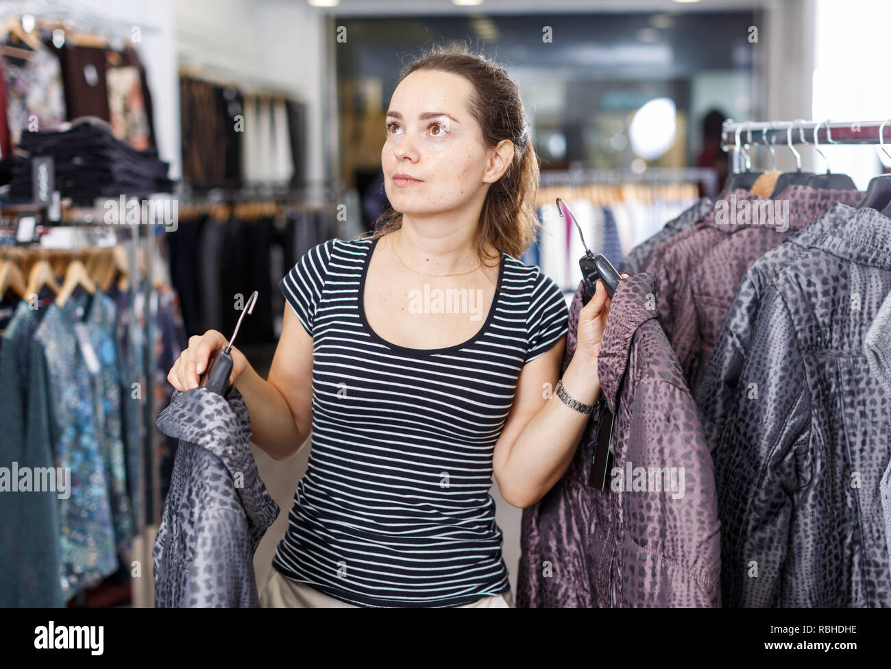 58853462d1 Young cheerful woman shopping in outerwear clothing boutique Stock ...
