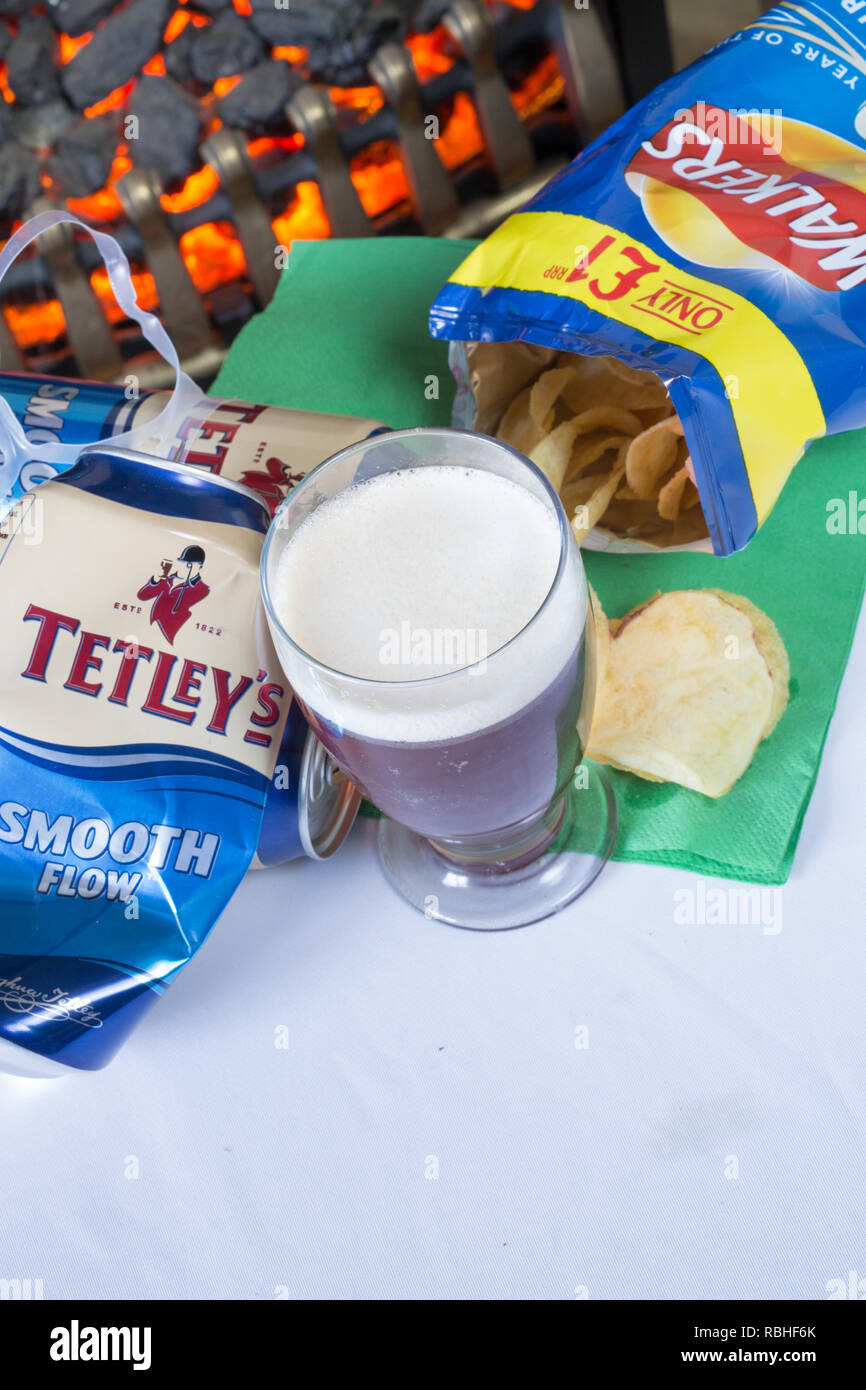 A glass of beer from a can of Tetley's Smooth flow bitter with Cheese and onion Walkers crisps. - Stock Image