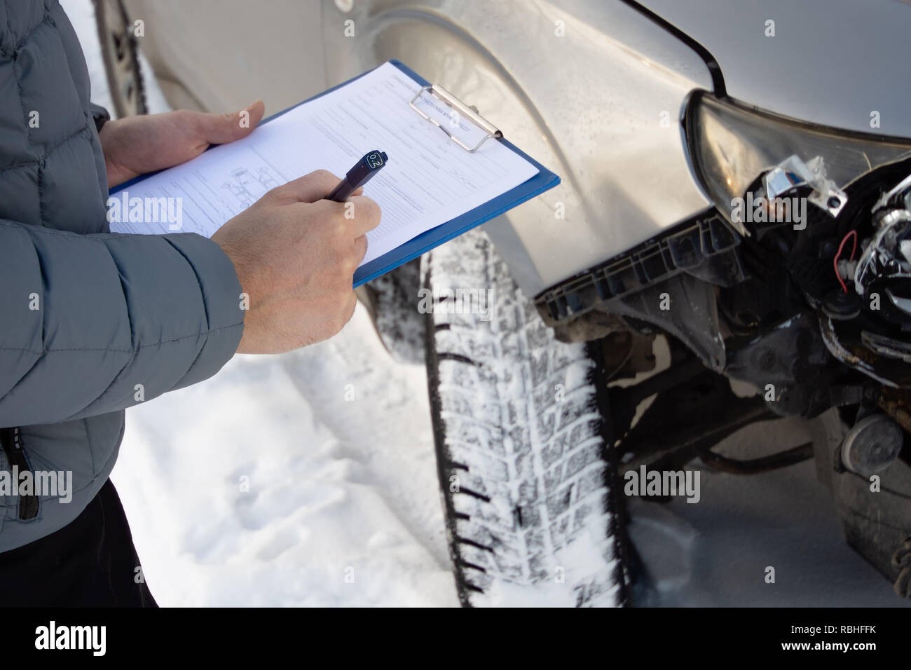 Insurance agent checking car after car accident and filling accident details form. Winter time. Focus on hands. - Stock Image