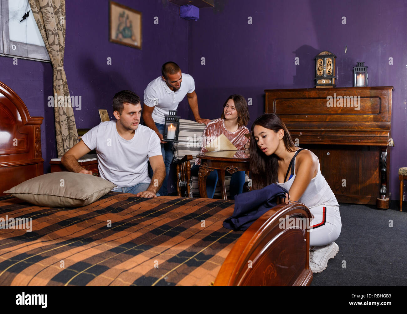 Group of young adults trying to find solution of quest in escape room with antique furnitures - Stock Image