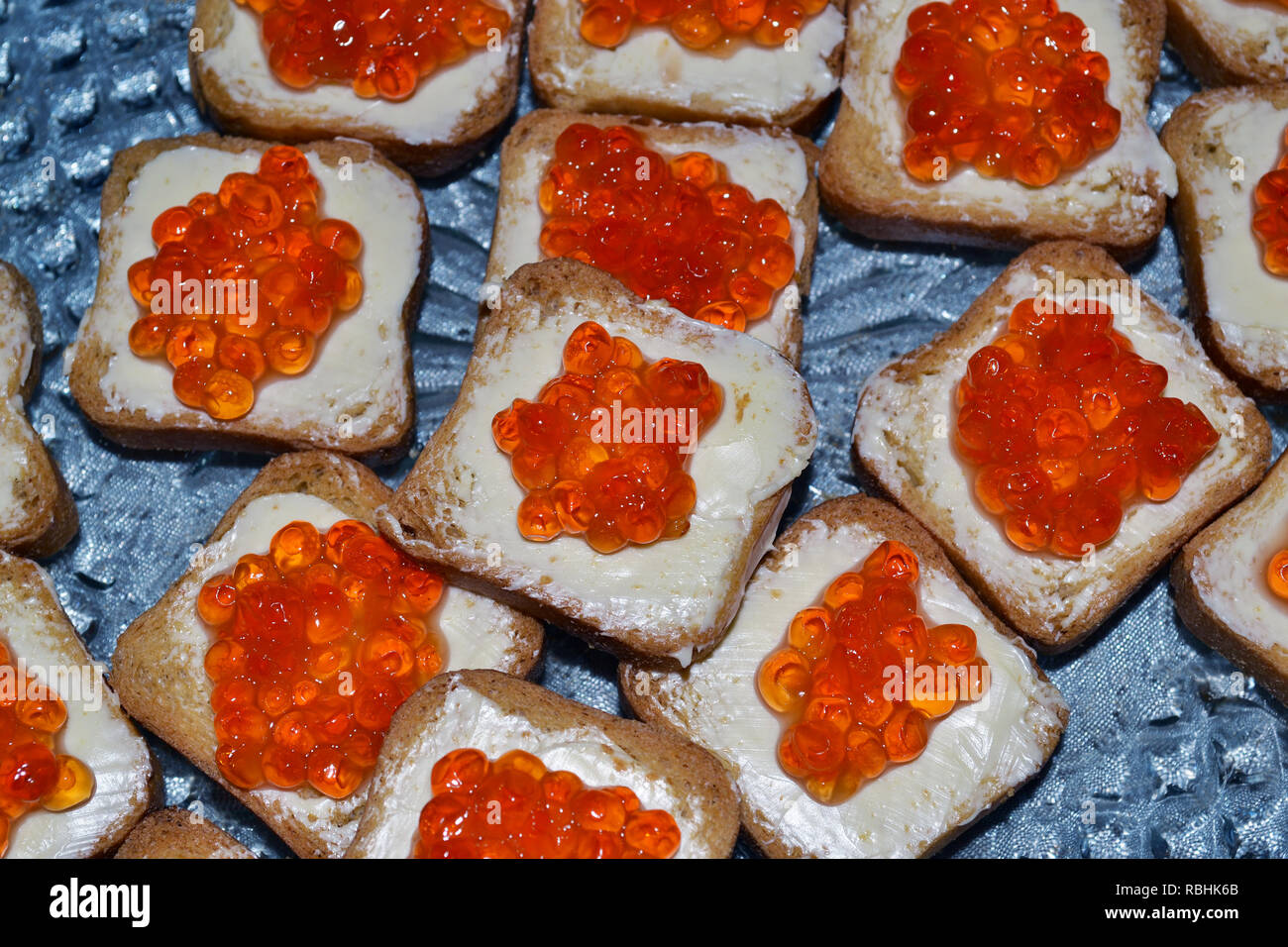 Top view of cheap looking red caviar canape made with rye bread and butter. - Stock Image