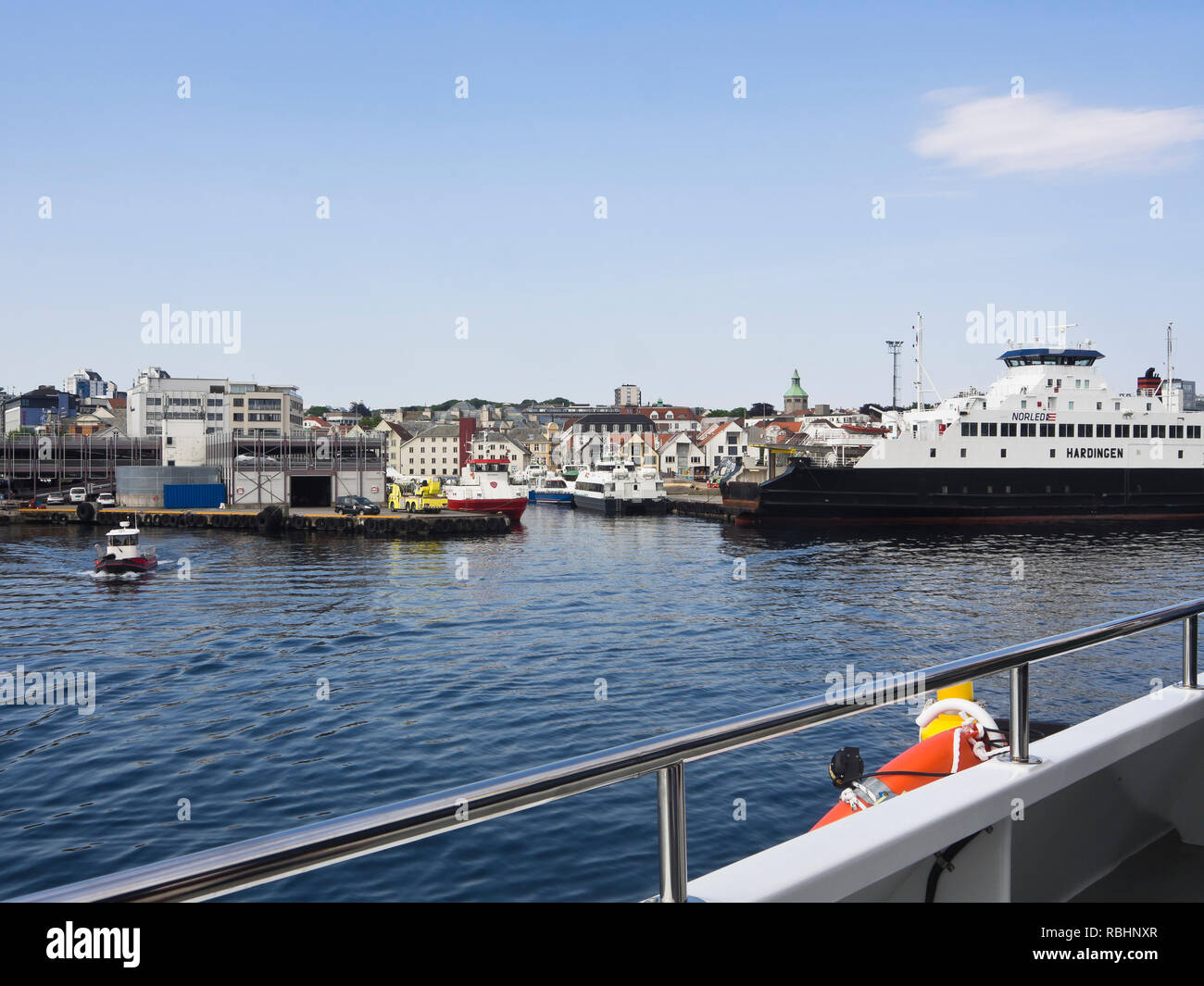 Entering the harbor in the Norwegian city of Stavanger by the North Sea, car ferry and the fire departments boat Vekteren along the quay - Stock Image