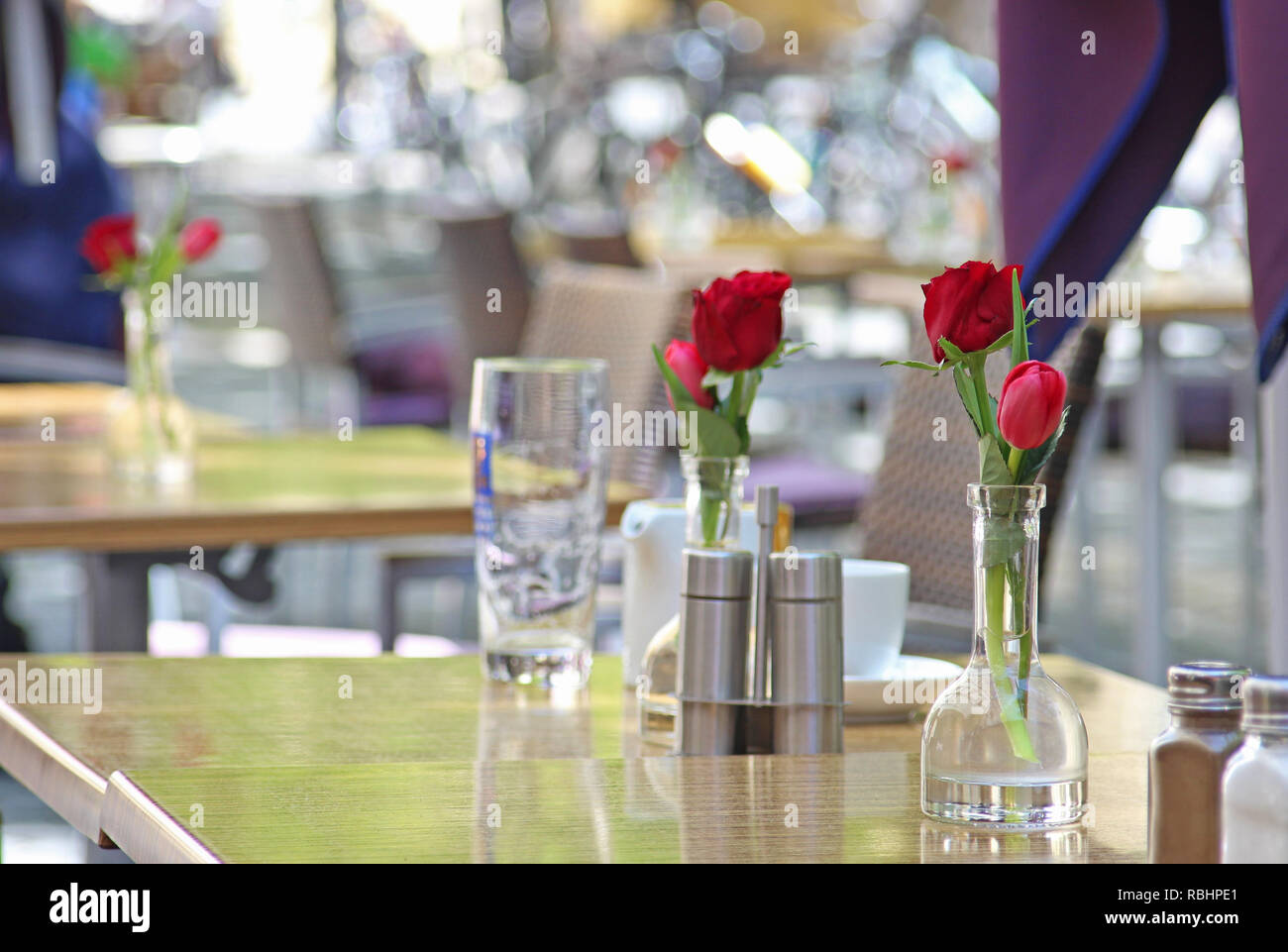 street cafe, in springtime, with red tulips on the tables - Stock Image