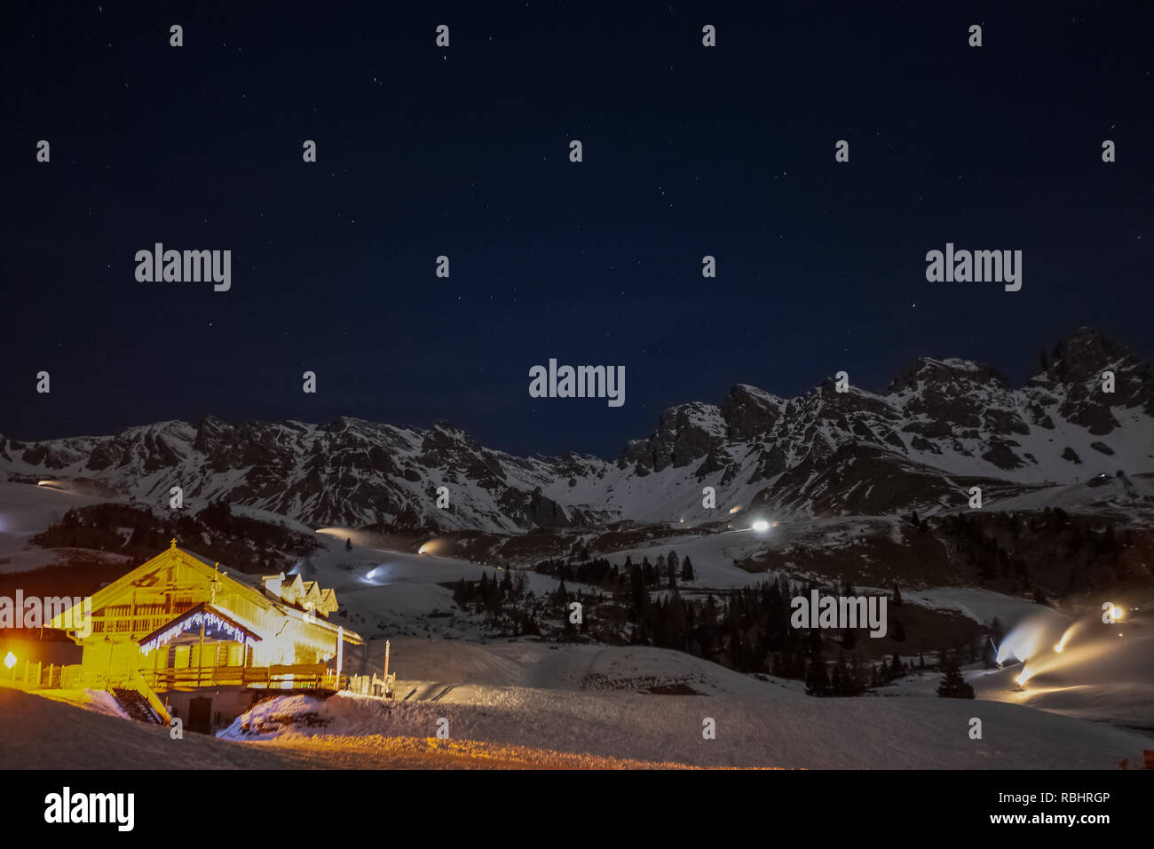 Illuminated chalet in the evening with snow cannons on the background preparing the ski slopes, Passo San Pellegrino, Dolomites, Italy Stock Photo