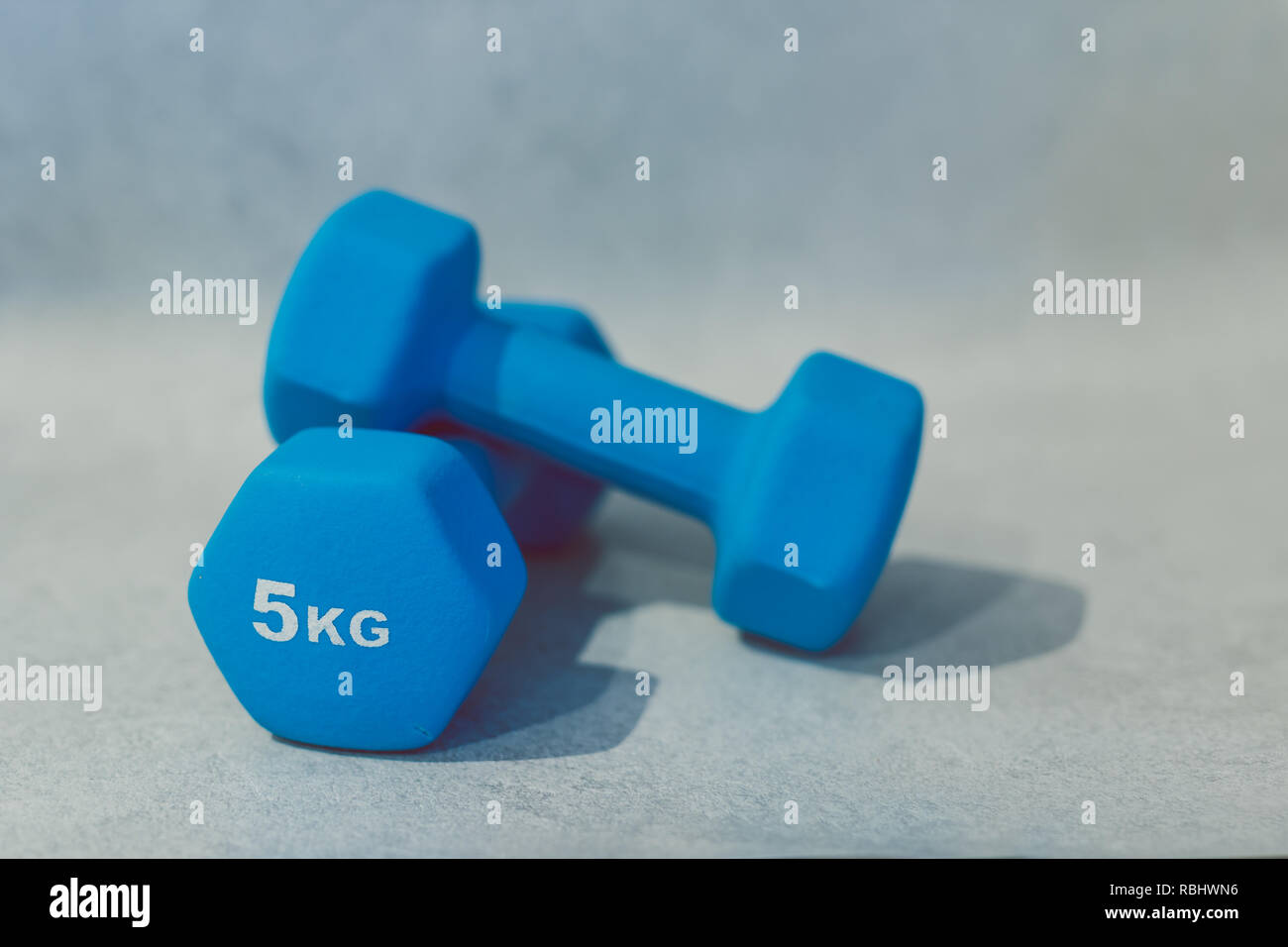 health and fitness resolutions, heavy dumbbells on concrete surface shot at shalow depth of field - Stock Image