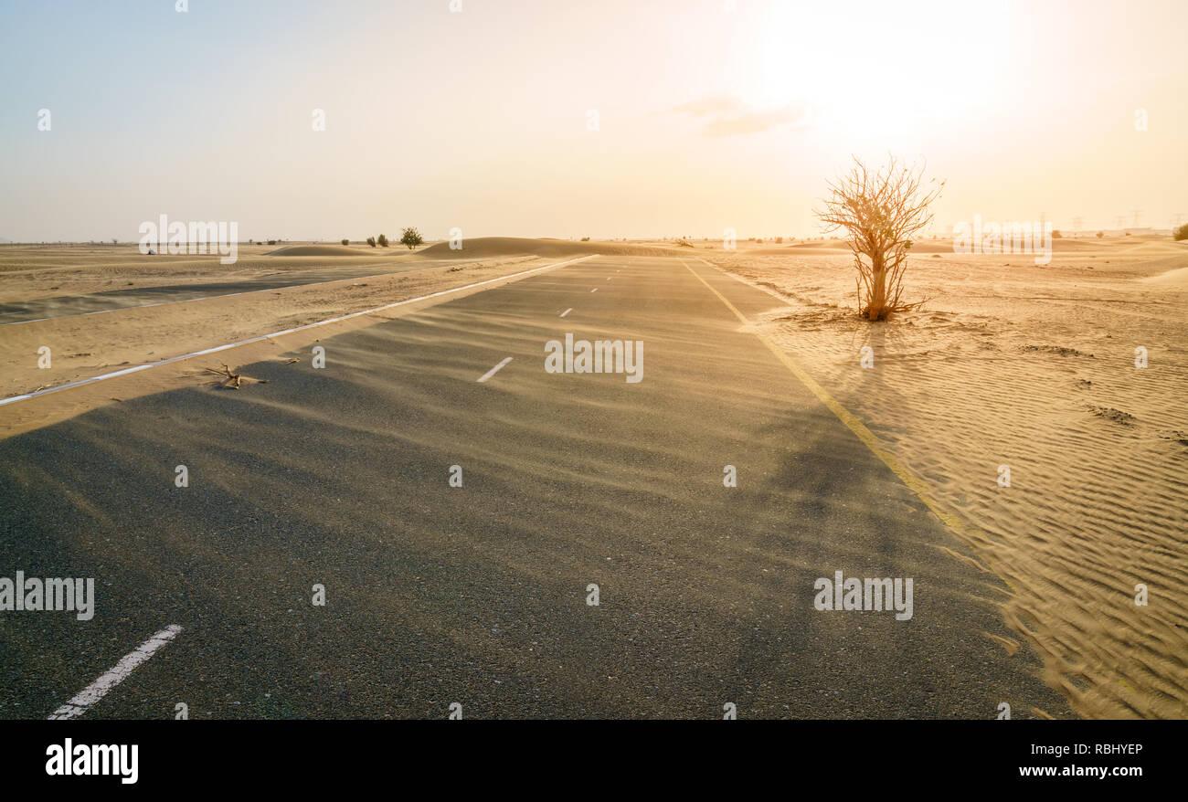 Sand is taking over a desert road near Dubai in UAE. Stock Photo