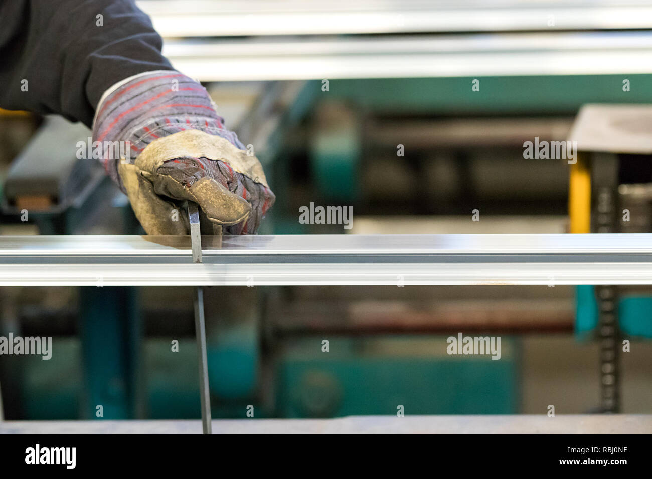 A man machine operator using safety gloves controlling the stretch of an aluminium profile with a squad. - Stock Image
