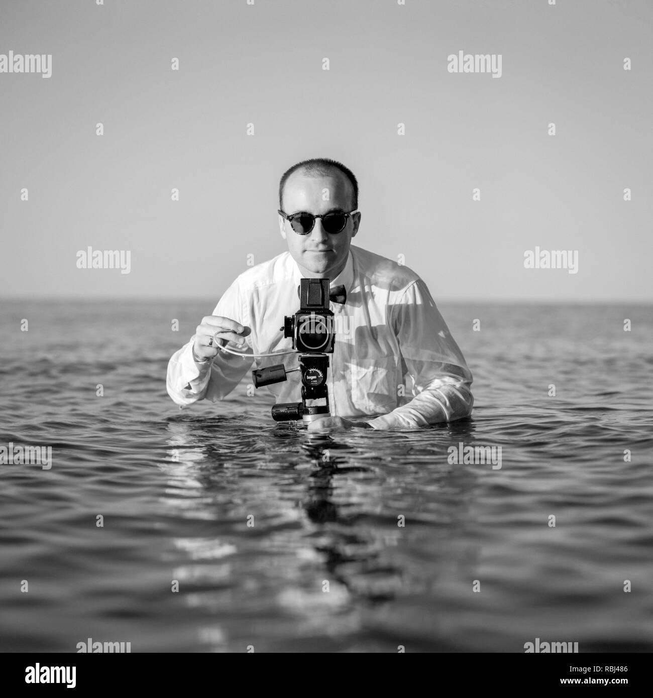 Young photographer standing in the water and holding medium format camera. Southampton Beach,  New York, US 40-45-years, 45-50-years, 50-59 Years, - Stock Image