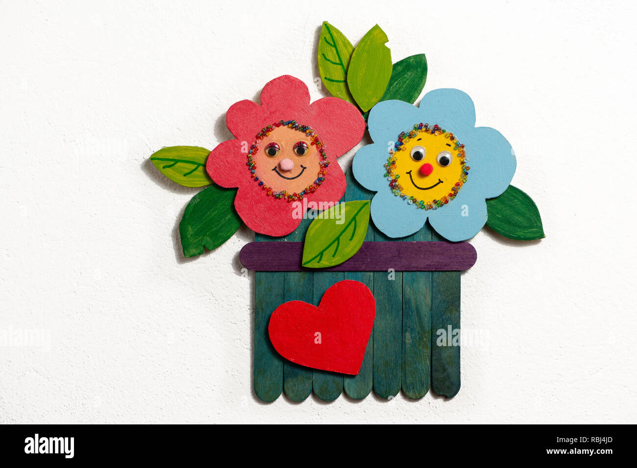 Colorful figure of flowers in a garden made of wood by a child, white background - Stock Image