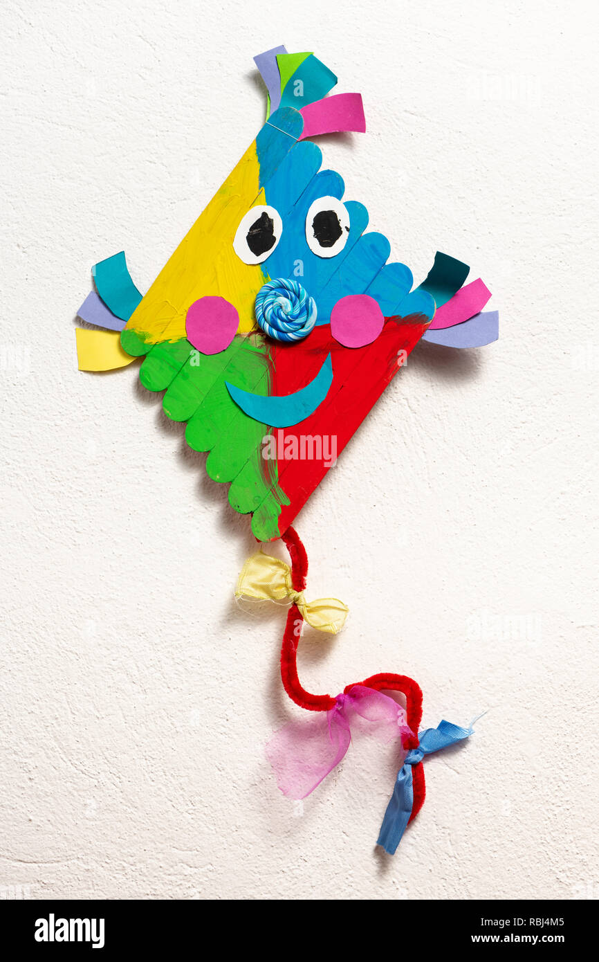 A colorful kite made of wood by a child, white background - Stock Image