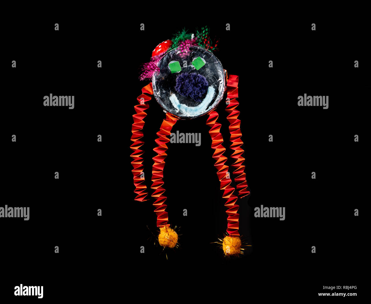 Figure of a funny colorful monster made of paper by a child, black background - Stock Image