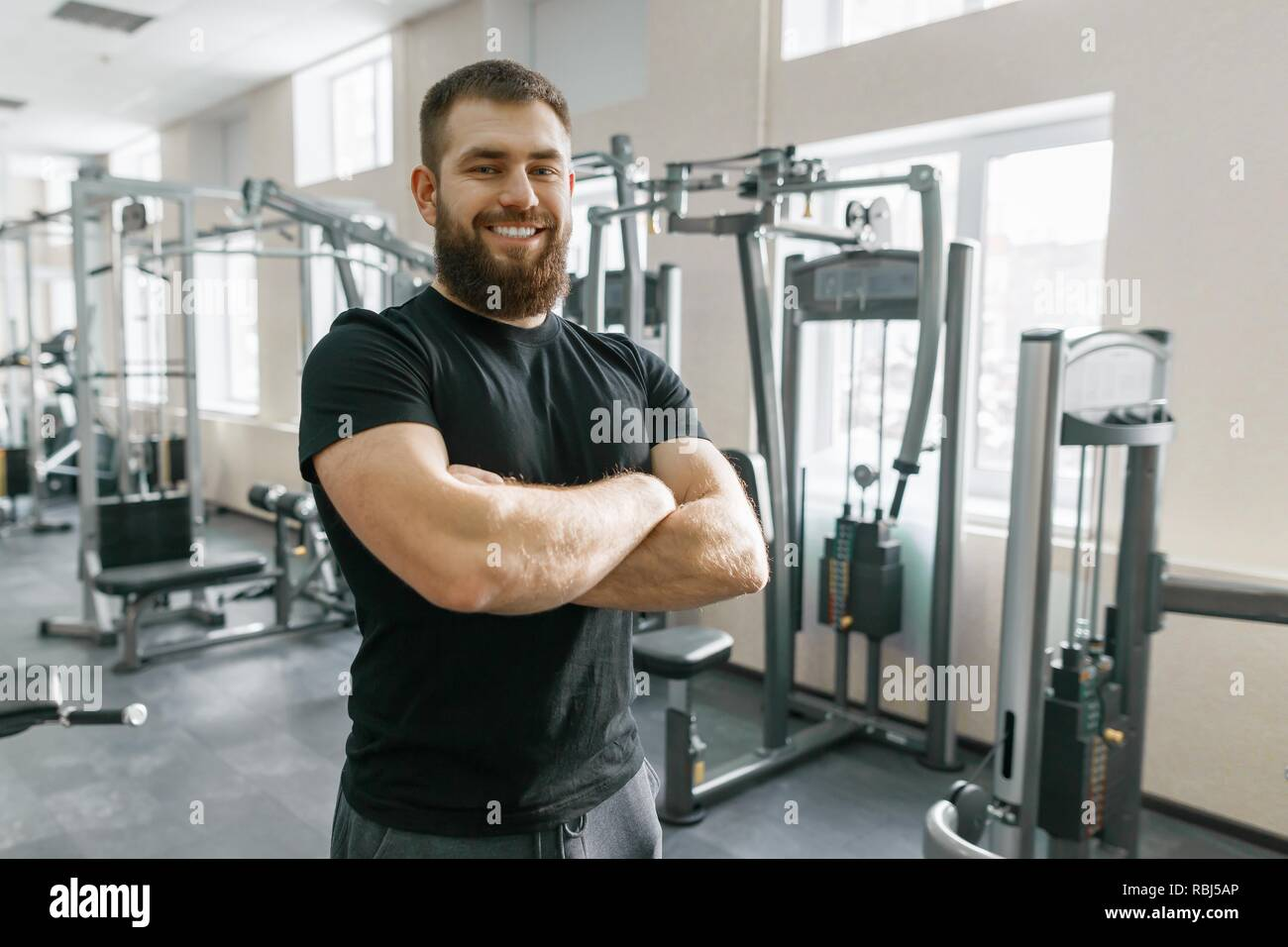 Smiling positive confident male personal instructor with arms crossed in fitness gym. - Stock Image
