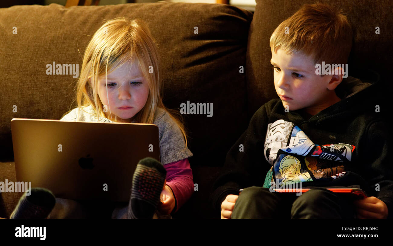A little girl (4 yrs old) sat on a sofa using a laptop computer while her brother (6 yrs old) watches. - Stock Image