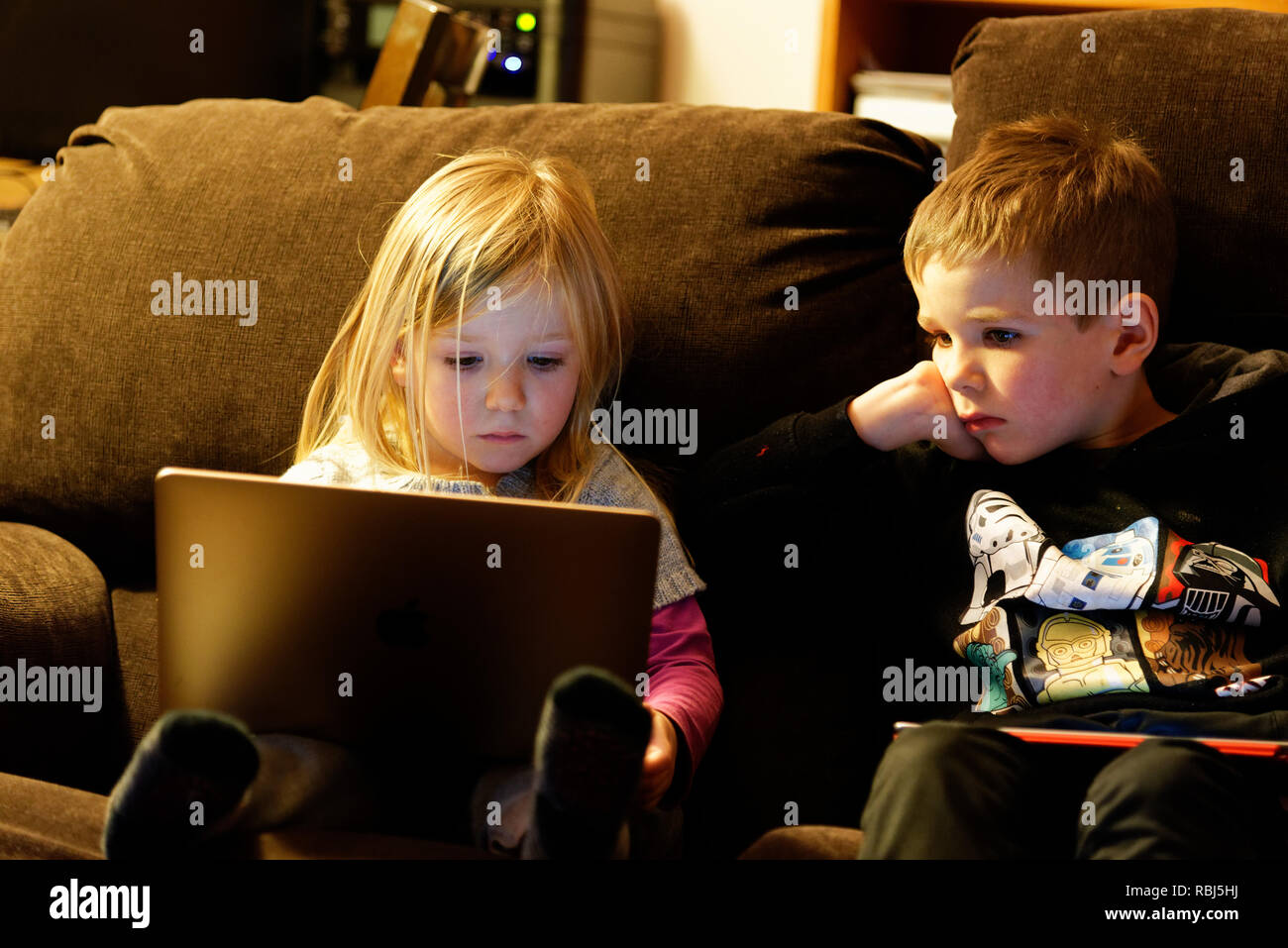 A little girl (4 yrs old) sat on a sofa using a laptop computer while her brother (6 yrs old) watches. Stock Photo