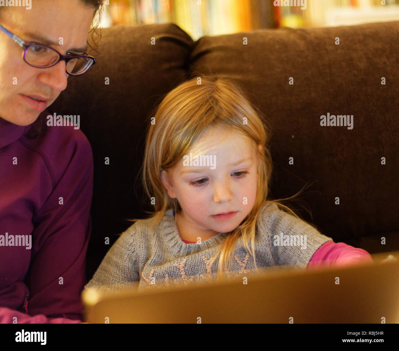 A little girl (4 yrs old) and her mum sat on a sofa using a laptop computer together - Stock Image