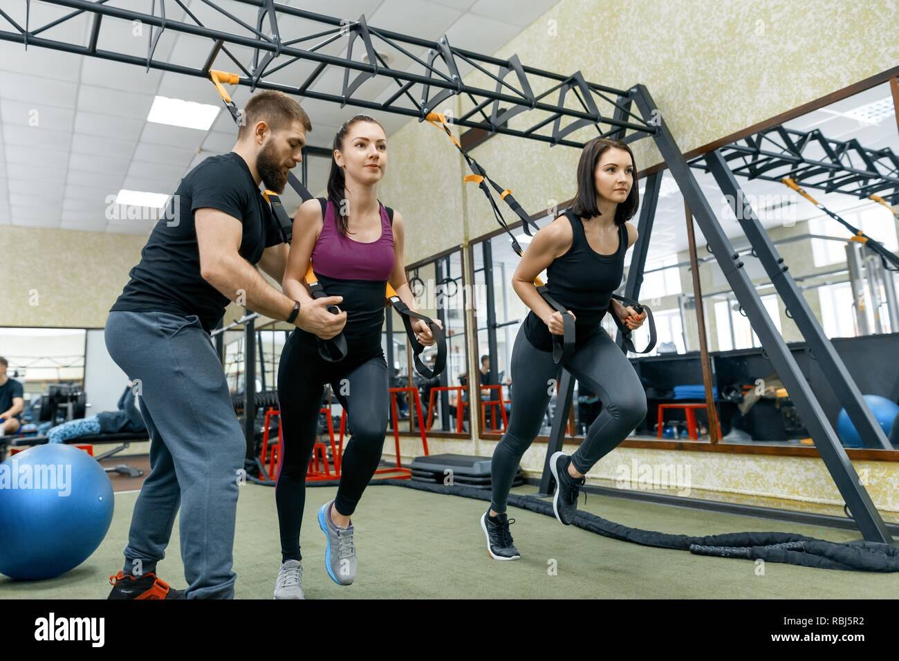 Fitness trainer coaching and helping women doing exercises on cross fit  using straps system in gym. Sport, teamwork, training, people concept Stock  Photo - Alamy