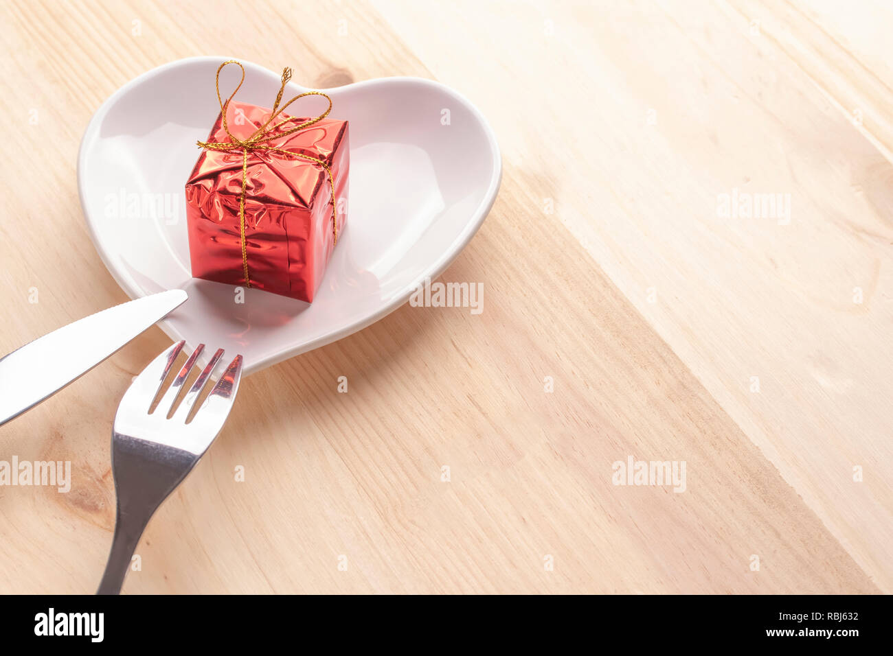A gift in bright red packaging on a white plate in the shape of a heart on a wooden background with a fork and knife. Festive background for Valentine - Stock Image