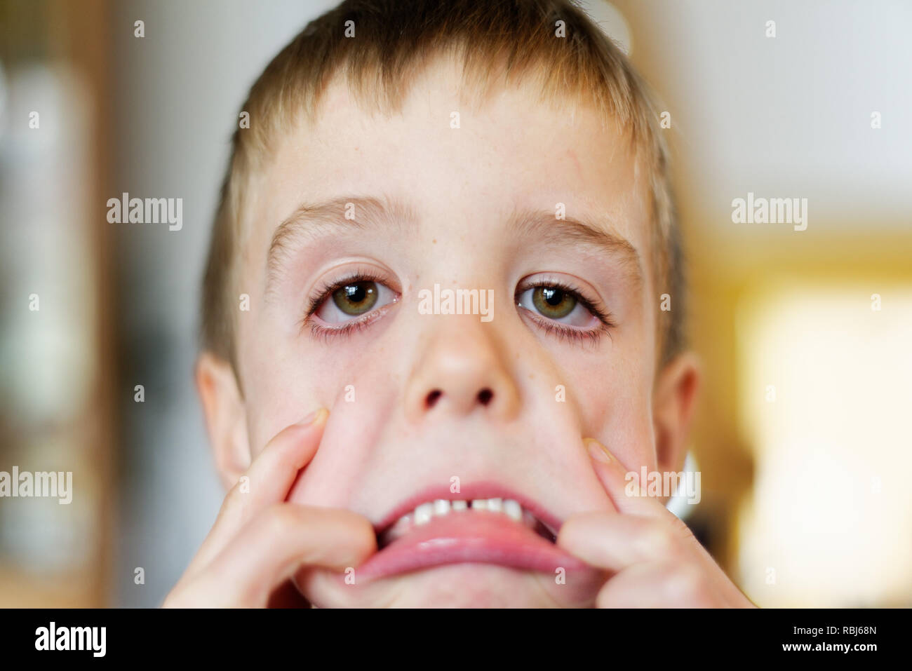 A young boy (6 yrs old) pulling faces at the camera - Stock Image