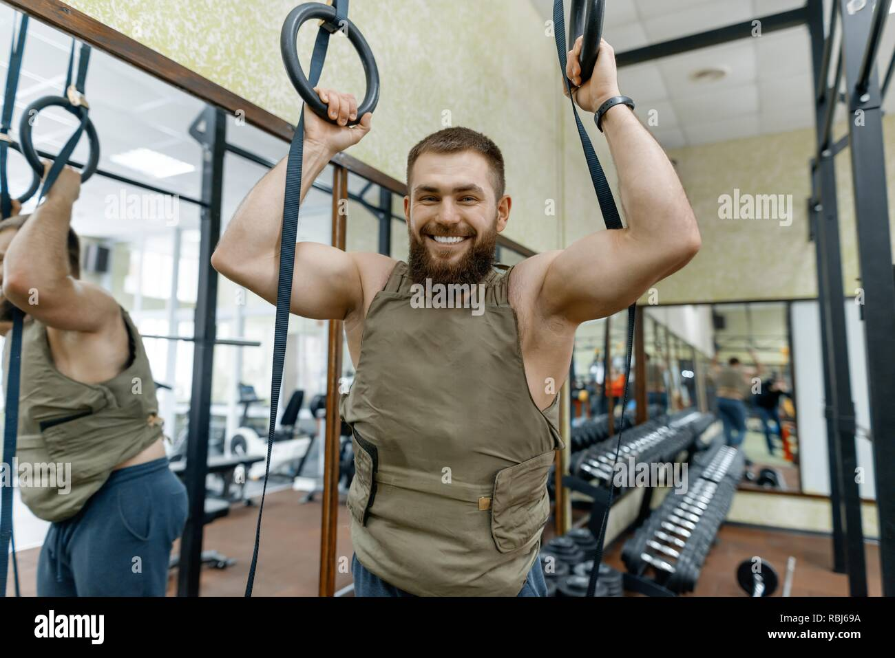 Portrait muscular caucasian bearded man dressed in weighted vest in the gym, military style. - Stock Image