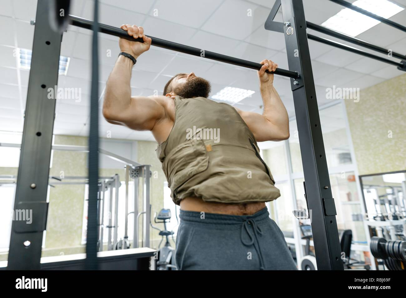 Military sport, muscular caucasian bearded adult man doing exercises in the gym dressed in bulletproof armored vest. - Stock Image