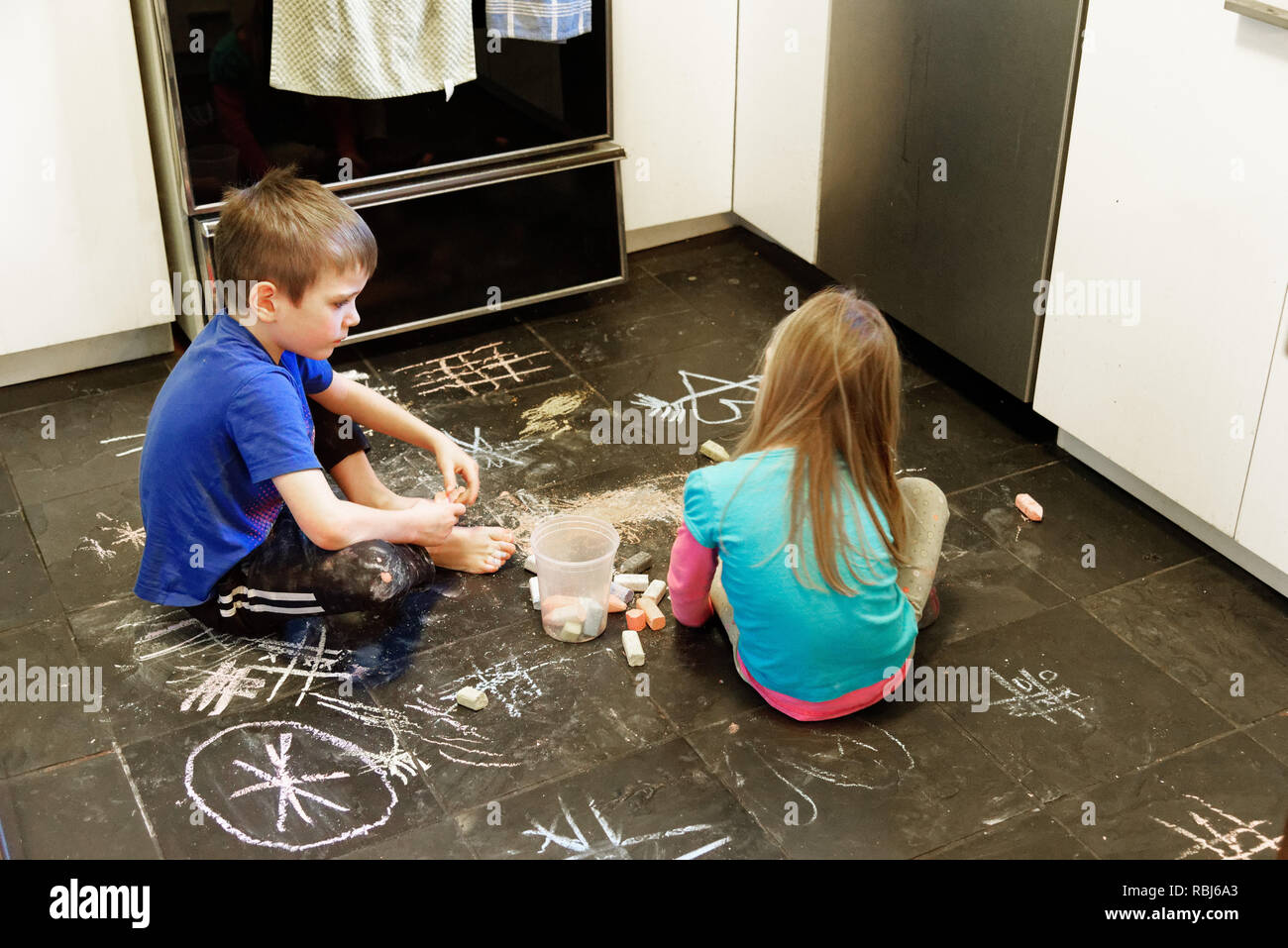 Two children using chalks to draw on a slate floor in their kitchen - Stock Image