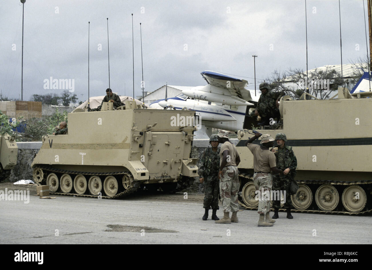 10th October 1993 U.S. Army soldiers stand next to their M577A1 Bradley command post armoured vehicles. They have just arrived at Mogadishu Airport in Somalia. Stock Photo