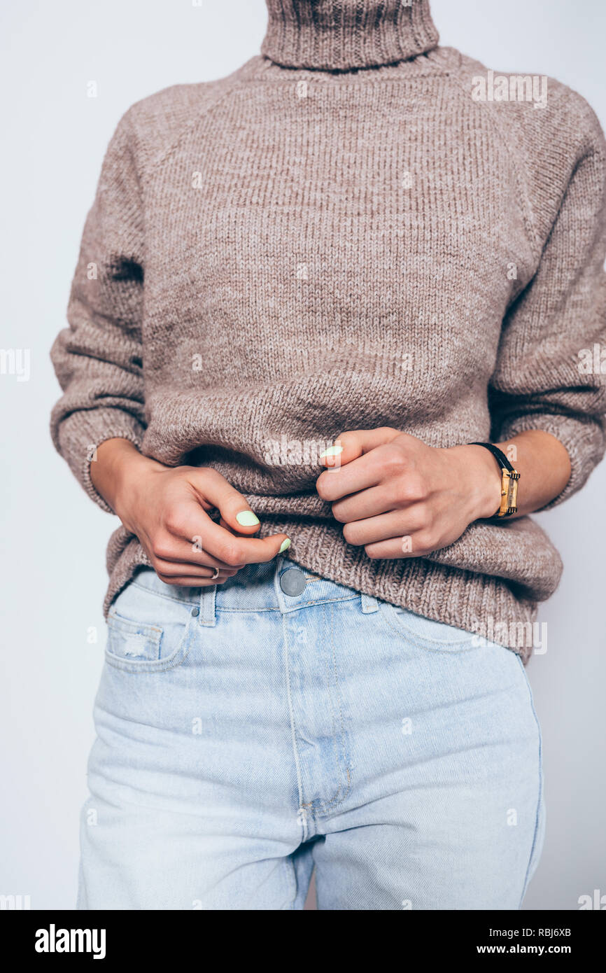 24934b57c2b Stylish elegant outfit for cold weather. Young woman wearing oversized  brown turtleneck sweater and blue boyfriend jeans.