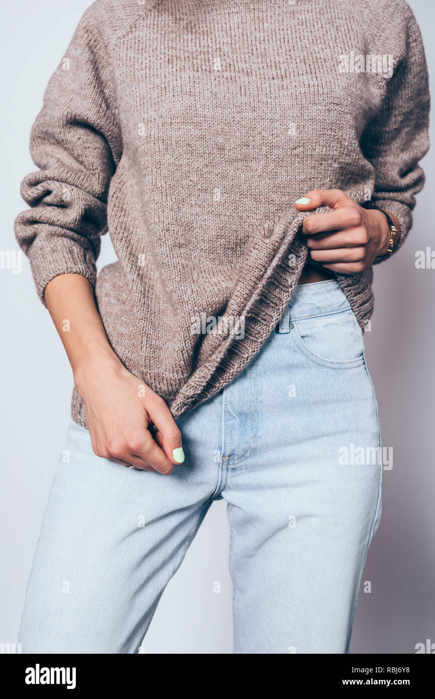 cc9ce54af44 Young female wearing trendy oversized brown sweater and blue boyfriend jeans.  Stylish casual outfit for cold weather.