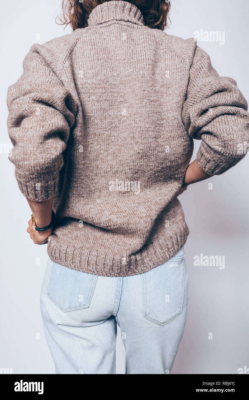 478f99b564a13a Rear view unrecognizable young woman wearing knitted brown oversized sweater  and blue jeans standing over white