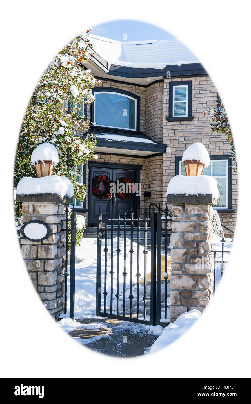 Luxury residential house entrance decorated for Christmass holiday. Family house in snow on winter season. White round borders - Stock Image