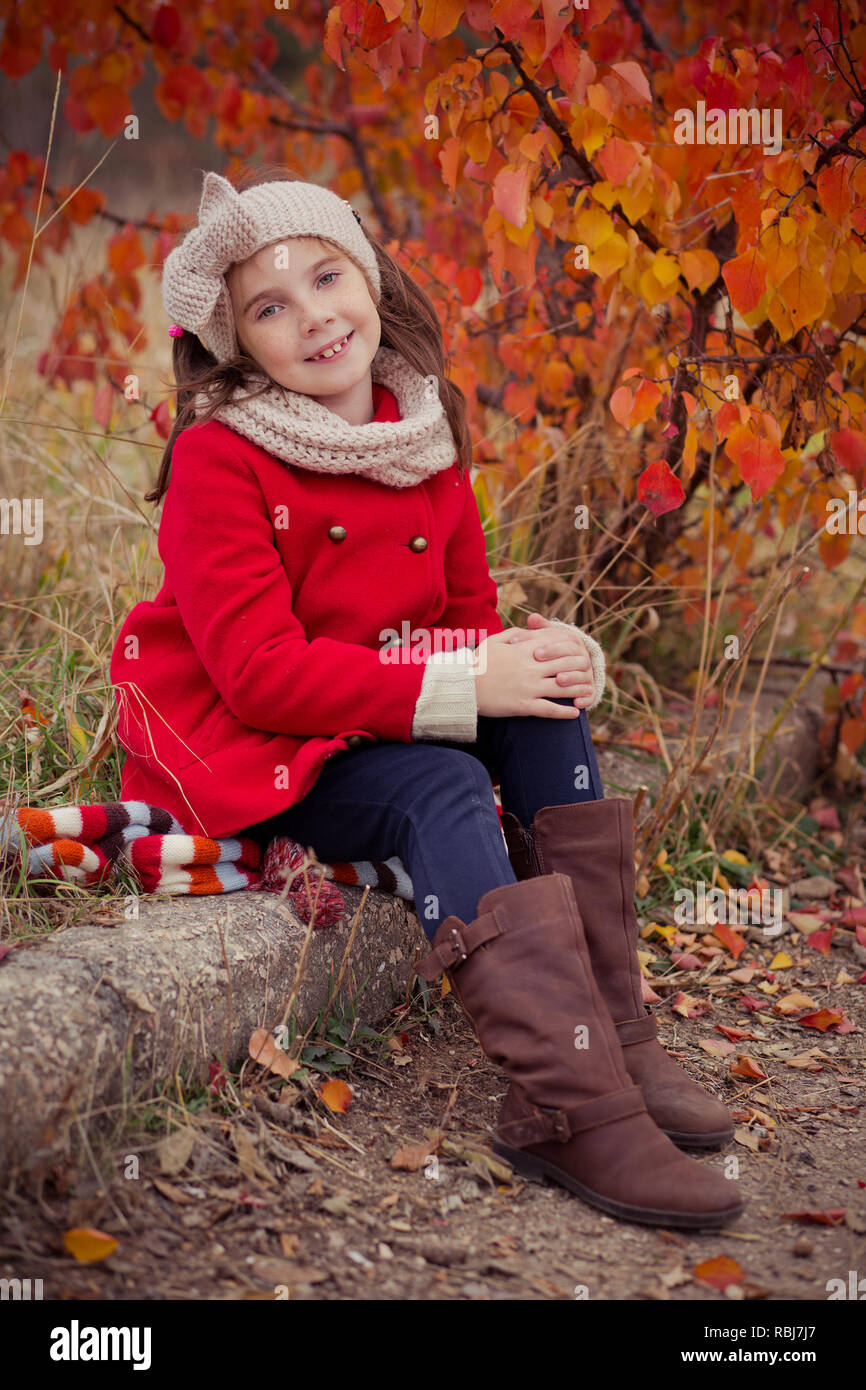 Cute young russian girl stylish dressed in warm red handmade jacket blue jeans boots and hooked headband scarf posing in autumn colorful forest pathwa - Stock Image