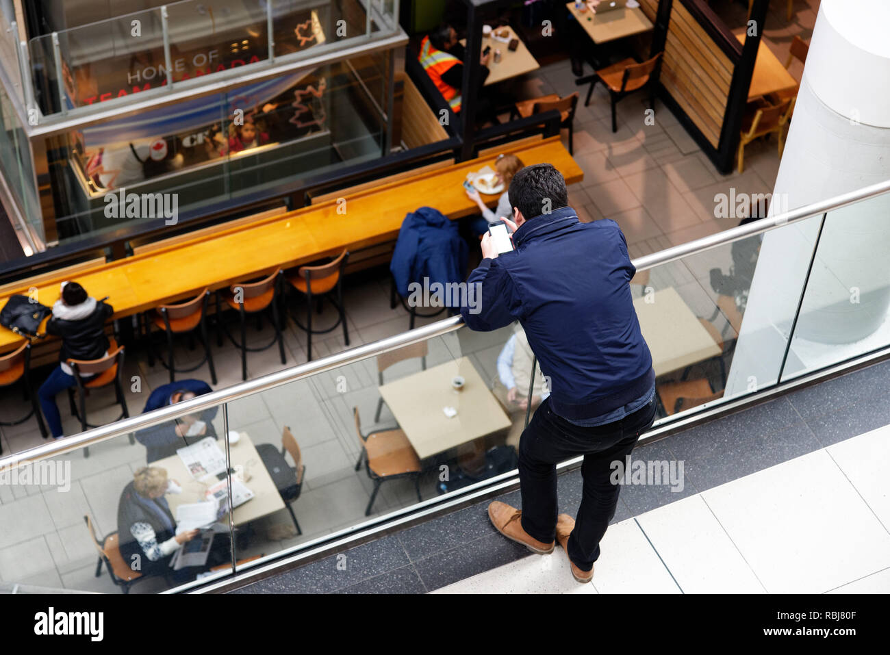 A man using a cellphone in a shopping mall - Stock Image