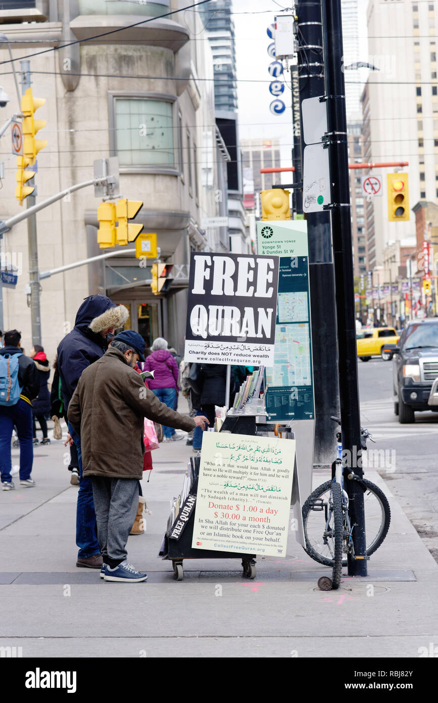 A muslim man at a street stand giving away free copies of the Koran, Toronto, Canada - Stock Image