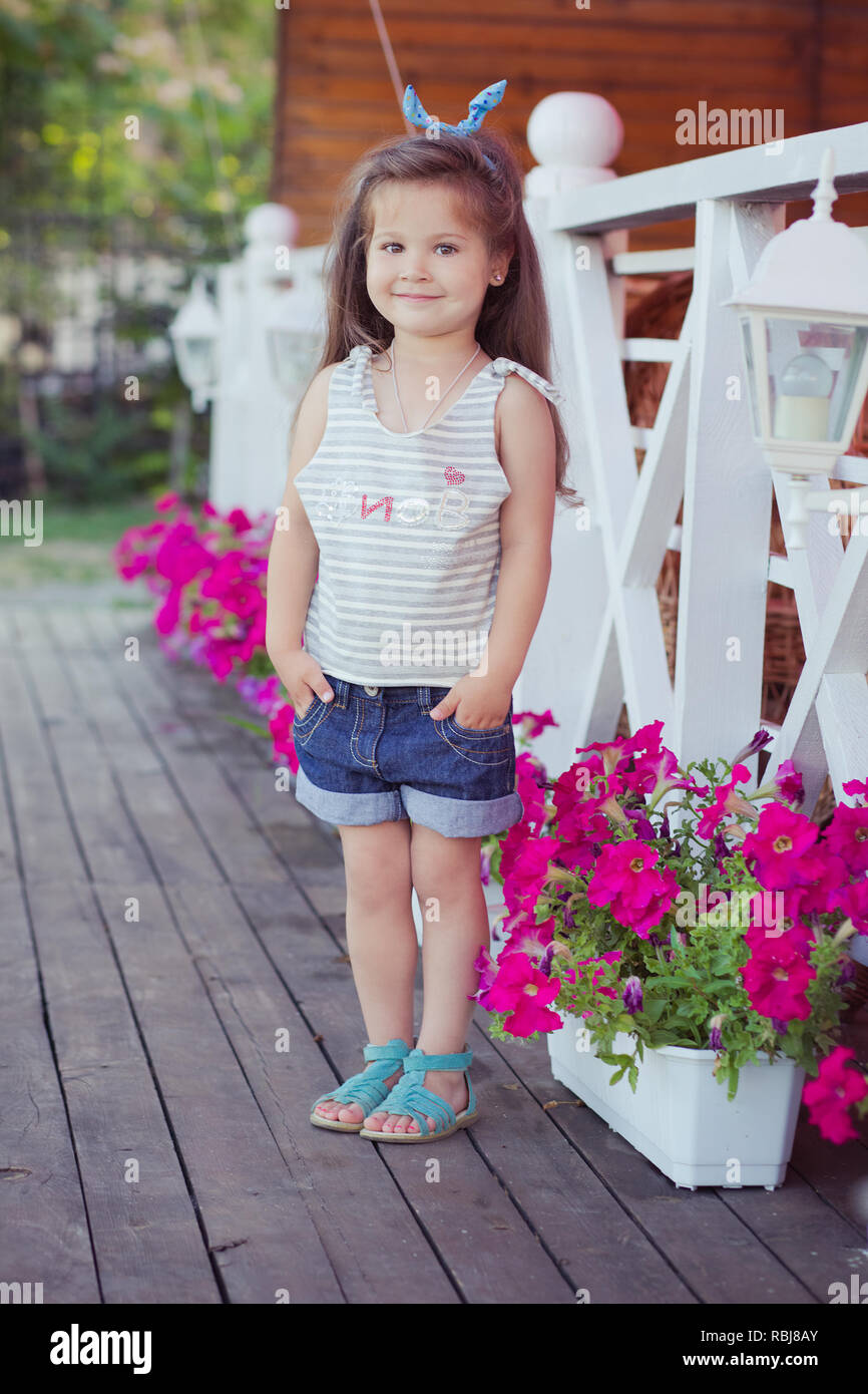Stylish beautifull cute baby girl with brunette hair posing on