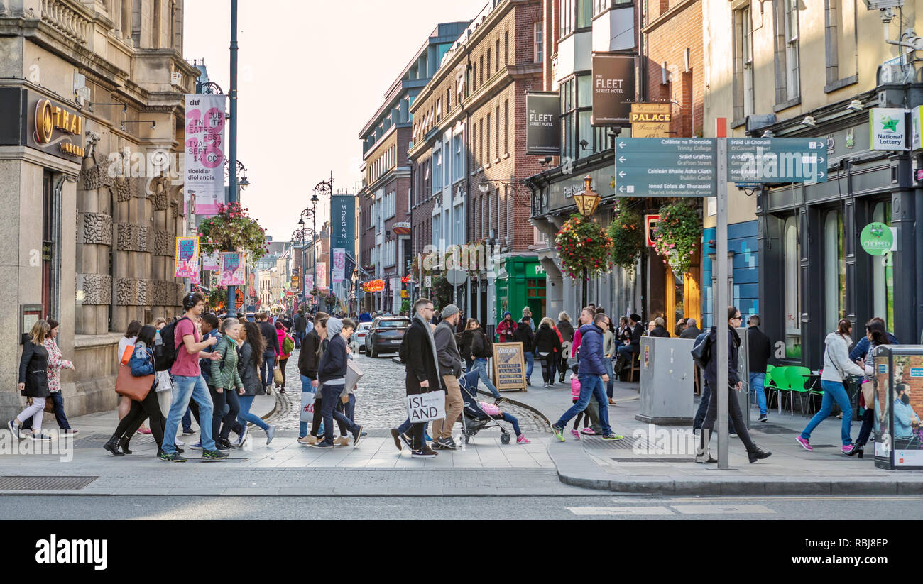 People, families, tourists walking and exploring Fleet St., a busy commercial street in Dublin, Ireland. - Stock Image