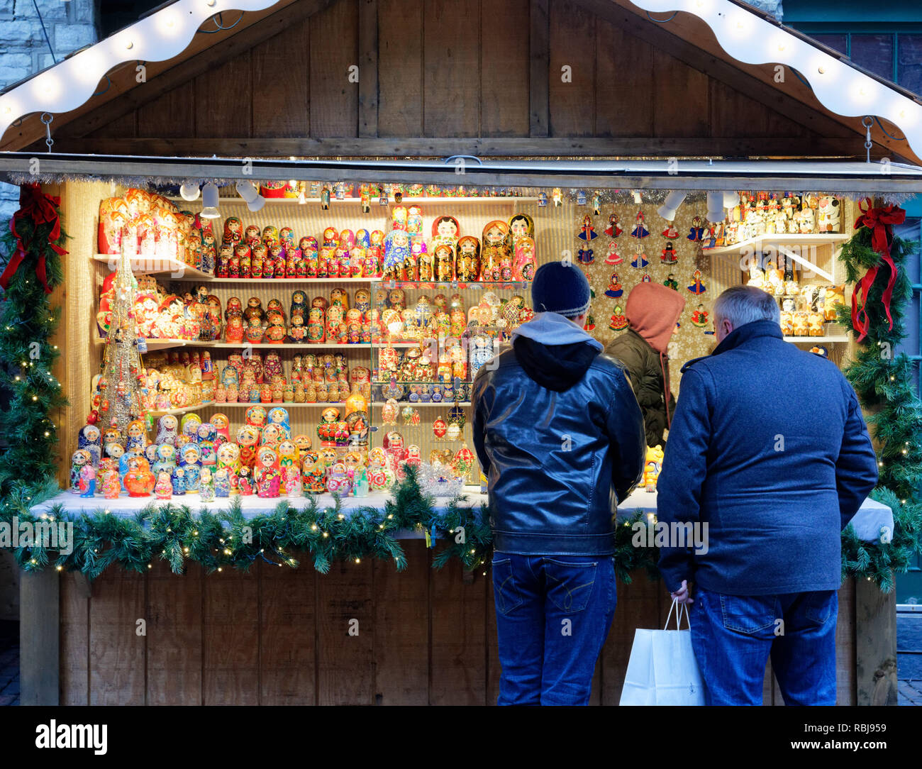 Two men looking at Russian Dolls in the Toronto Christmas Market in the Distillery District - Stock Image