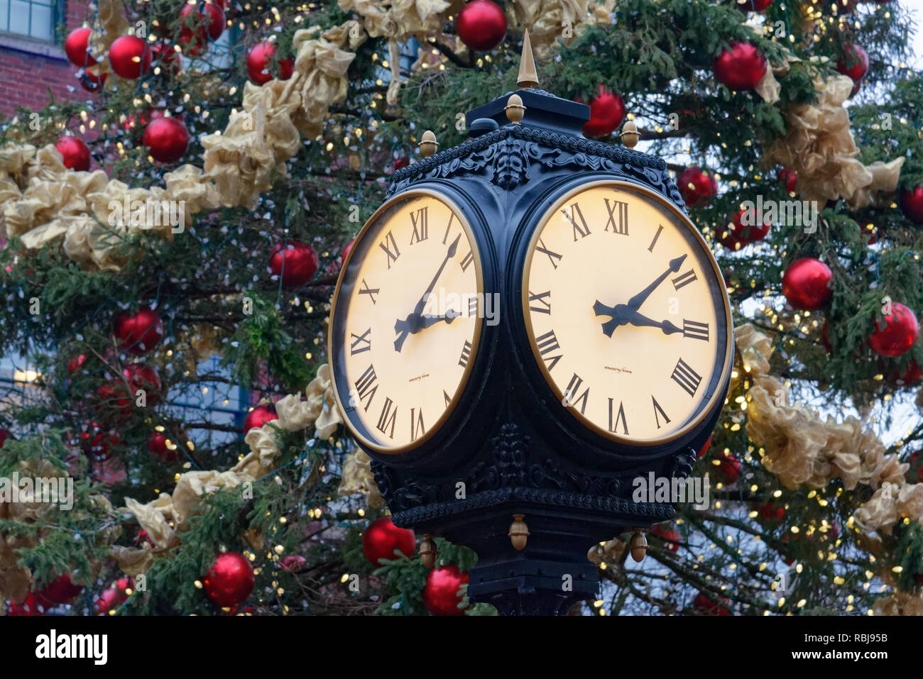 The clock and Christmas Tree in Toronto Christmas Market in the Distillery District - Stock Image