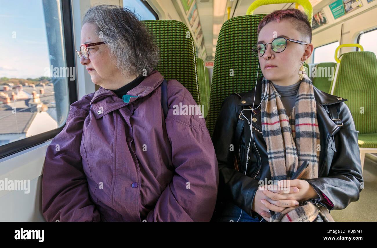 Riders on the DART, public transportation, in Dublin, Ireland. - Stock Image