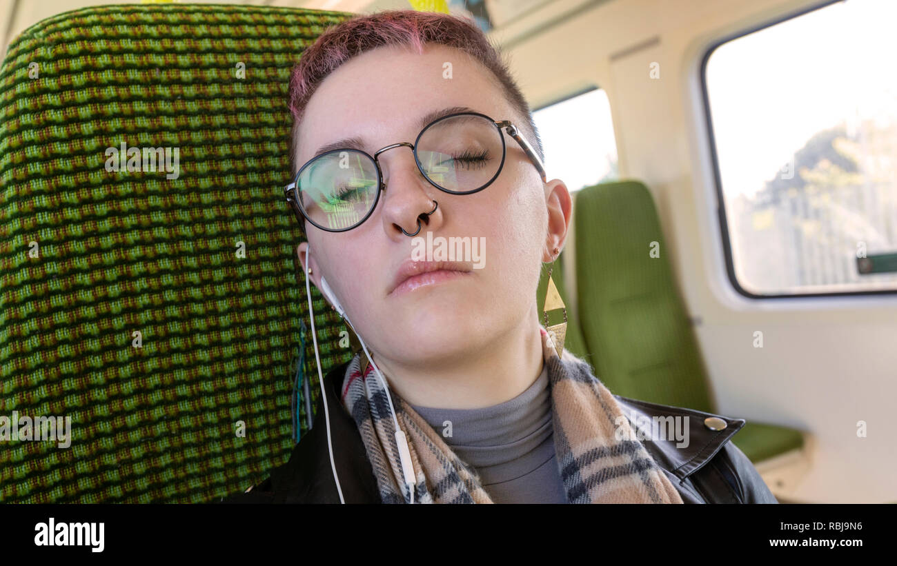 Young woman resting her eyes and riding on the DART, public transportation, in Dublin, Ireland. - Stock Image
