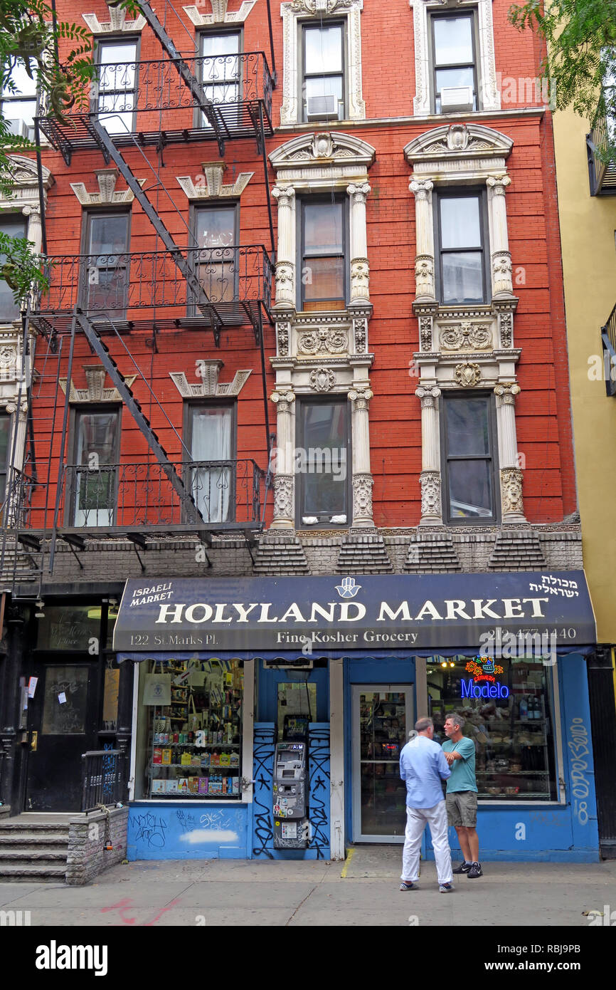 Two men outside Holyland Market, 122 St Marks Place, East Village, New York, NYC, NY, USA Stock Photo
