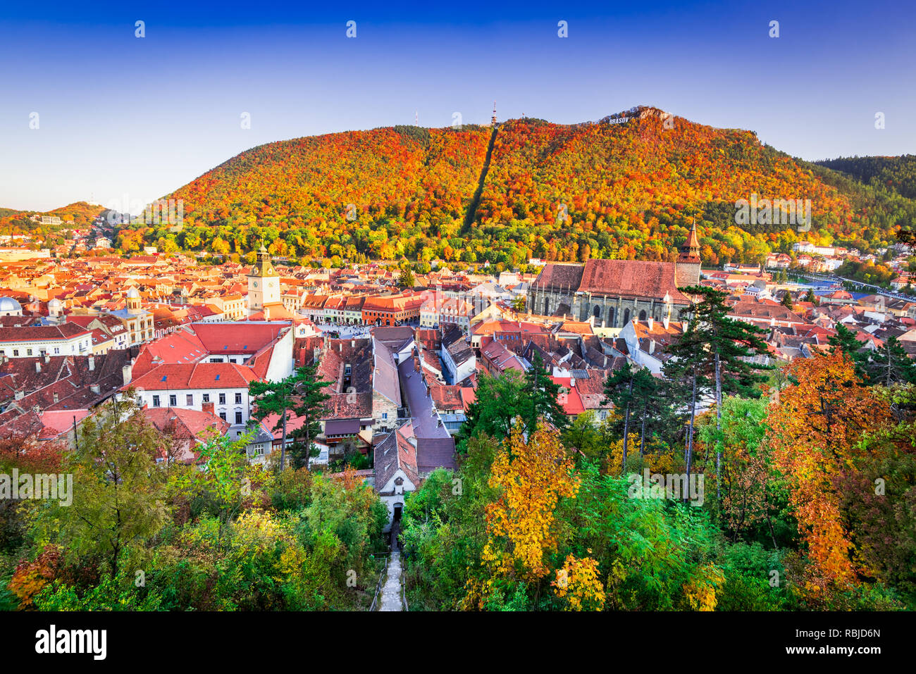 Brasov, Romanian with autumn sunny colors on medieval Transylvania and Carpathian Mountains range. - Stock Image